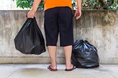Sac de déchets de transport de jeune homme photographie stock libre de droits