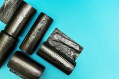 Sac de déchets noir d'isolement sur le fond bleu images stock