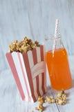 Sac de maïs éclaté de caramel avec le soda orange image stock