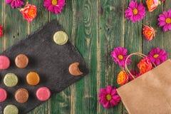 Sac de papier avec des fleurs le fond en bois, l'heure de achat ou l'heure à vendre Photos stock