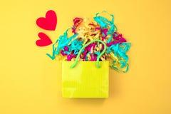 Sac de papier avec les flammes colorées sur un concept rouge de coeur de fond jaune lumineux de Valentine& x27 ; jour de s photos stock
