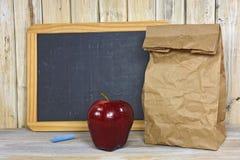 Sac de papier de Brown avec la pomme et le tableau rouges image stock