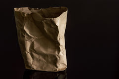 Sac de papier de Brown d'isolement sur le fond noir Photo stock