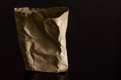 Sac de papier de Brown d'isolement sur le fond noir photo stock