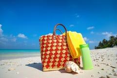 Sac de plage d'été avec la coquille, serviette sur la plage sablonneuse Photographie stock libre de droits