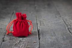 Sac de tissu rouge lumineux sur une table en bois foncée Images stock