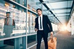 Sac de transport d'homme d'affaires et téléphone intelligent à l'aéroport Photographie stock