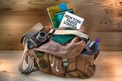 Sac photographique avec les cartes, le guide touristique et les objets utiles pour le voyage et le tourisme Photo stock