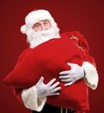 Sac rouge énorme à embrassement de Santa Claus avec des cadeaux Images libres de droits