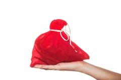 Sac rouge avec des présents sur la main de femme d'isolement sur le fond blanc Photo stock