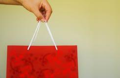 Sac rouge de cadeau dans la main de l'homme Image stock