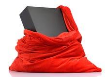 Sac rouge du père noël avec la boîte noire de cadeau Image stock