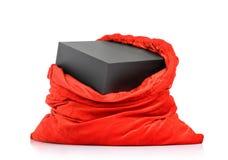 Sac rouge du père noël avec la boîte noire de cadeau sur le fond blanc Le fichier contient un chemin à l'isolement Photos stock