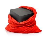 Sac rouge du père noël avec la boîte noire de cadeau sur le fond blanc Le fichier contient un chemin à l'isolement Photographie stock libre de droits