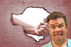 Sacador del asalto de la sorpresa del agujero en ataque de la pared de ladrillo imagen de archivo libre de regalías