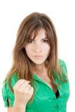 Sacador que lanza de la mujer morena enojada joven con el puño a la cámara Fotografía de archivo