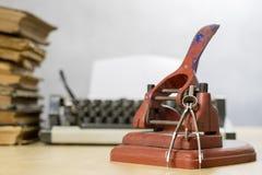 Sacador viejo del papel de la oficina en una tabla de madera Accesorios de la oficina encendido Imagen de archivo