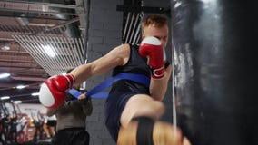 Sacadores del entrenamiento del hombre del boxeador por el entrenamiento personal del bolso del boxeo junto en club del gimnasio  almacen de metraje de vídeo