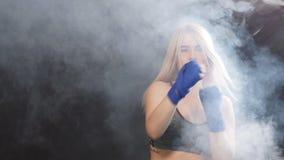Sacadores practicantes de la mujer hermosa joven mientras que se coloca en el gimnasio oscuro, cámara lenta almacen de video