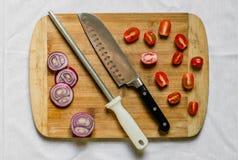 Sacapuntas de cuchillo y un cuchillo del cocinero en una tabla de cortar con las verduras foto de archivo libre de regalías