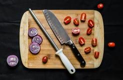 Sacapuntas de cuchillo y un cuchillo del cocinero en una tabla de cortar con las verduras imagen de archivo