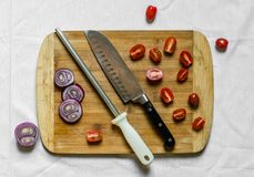 Sacapuntas de cuchillo y un cuchillo del cocinero en una tabla de cortar con las verduras foto de archivo