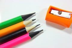 Sacapuntas de lápiz y lápices coloreados en una pila Fotos de archivo libres de regalías