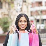 Sacchetti della spesa attraenti sorridenti della tenuta della donna di Shoping. Fotografie Stock Libere da Diritti