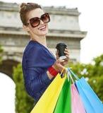 Sacchetti della spesa d'avanguardia sorridenti del womanwith vicino ad Arc de Triomphe Fotografia Stock