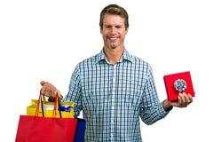 Sacchetti della spesa della tenuta dell'uomo e contenitore di regalo felici Immagine Stock Libera da Diritti