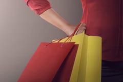 Sacchetti della spesa della tenuta della donna di acquisto in suo lombo Fotografia Stock Libera da Diritti