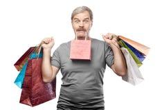 Sacchetti della spesa maturi sorpresi della tenuta dell'uomo isolati su bianco Fotografia Stock