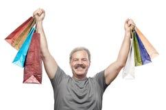 Sacchetti della spesa maturi sorridenti della tenuta dell'uomo isolati su bianco Fotografie Stock Libere da Diritti