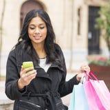 Sacchetti della spesa sorridenti del messaggio e della tenuta della lettura della donna. Immagine Stock