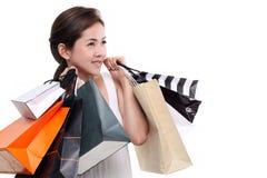 Sacchetti della spesa sorridenti felici asiatici della tenuta della donna di acquisto isolati su fondo bianco Fotografie Stock Libere da Diritti