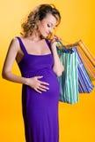 Sacchetti di acquisto belli della holding della donna incinta Immagini Stock