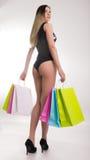 Sacchetti di acquisto della holding della donna di acquisto Primo piano di belle gambe delle donne in costume da bagno e tacchi a Fotografie Stock