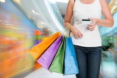Sacchetti di acquisto della holding della donna e carta di credito immagine stock