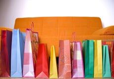 Sacchetti di acquisto sulla priorità bassa del sofà Immagini Stock Libere da Diritti