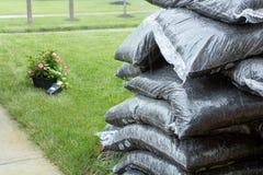 Sacchetti di plastica impilati di pacciame e dei fiori in pioggia immagini stock