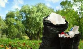 Sacchetti neri pieni di plastica e del cestino per la carta straccia Immagini Stock Libere da Diritti