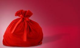 Sacchetto del regalo della Santa su colore rosso Fotografie Stock Libere da Diritti