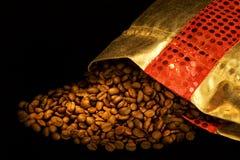 Sacchetto dell'oro con i chicchi di caffè fotografia stock