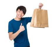 Sacchetto della spesa asiatico della tenuta dell'uomo con il pollice sul gesto Immagini Stock