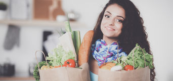 Sacchetto della spesa della drogheria della tenuta della giovane donna con le verdure Stando nella cucina Immagini Stock