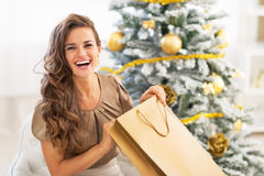 Sacchetto della spesa di apertura della donna vicino all'albero di Natale Immagini Stock
