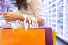 Sacchetto della spesa di modo della tenuta della donna variopinto in centro commerciale, fine su Y Fotografie Stock Libere da Diritti