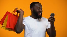 Sacchetto della spesa e smartphone di tenuta maschii neri emozionanti, servizi della parte posteriore dei contanti video d archivio