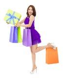 Sacchetto della spesa sorridente della tenuta della giovane donna e un contenitore di regalo Immagini Stock