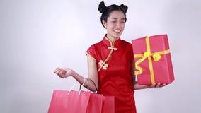 Sacchetto della spesa della tenuta della donna e contenitore di regalo rosso nella celebrazione cinese del nuovo anno di concetto archivi video